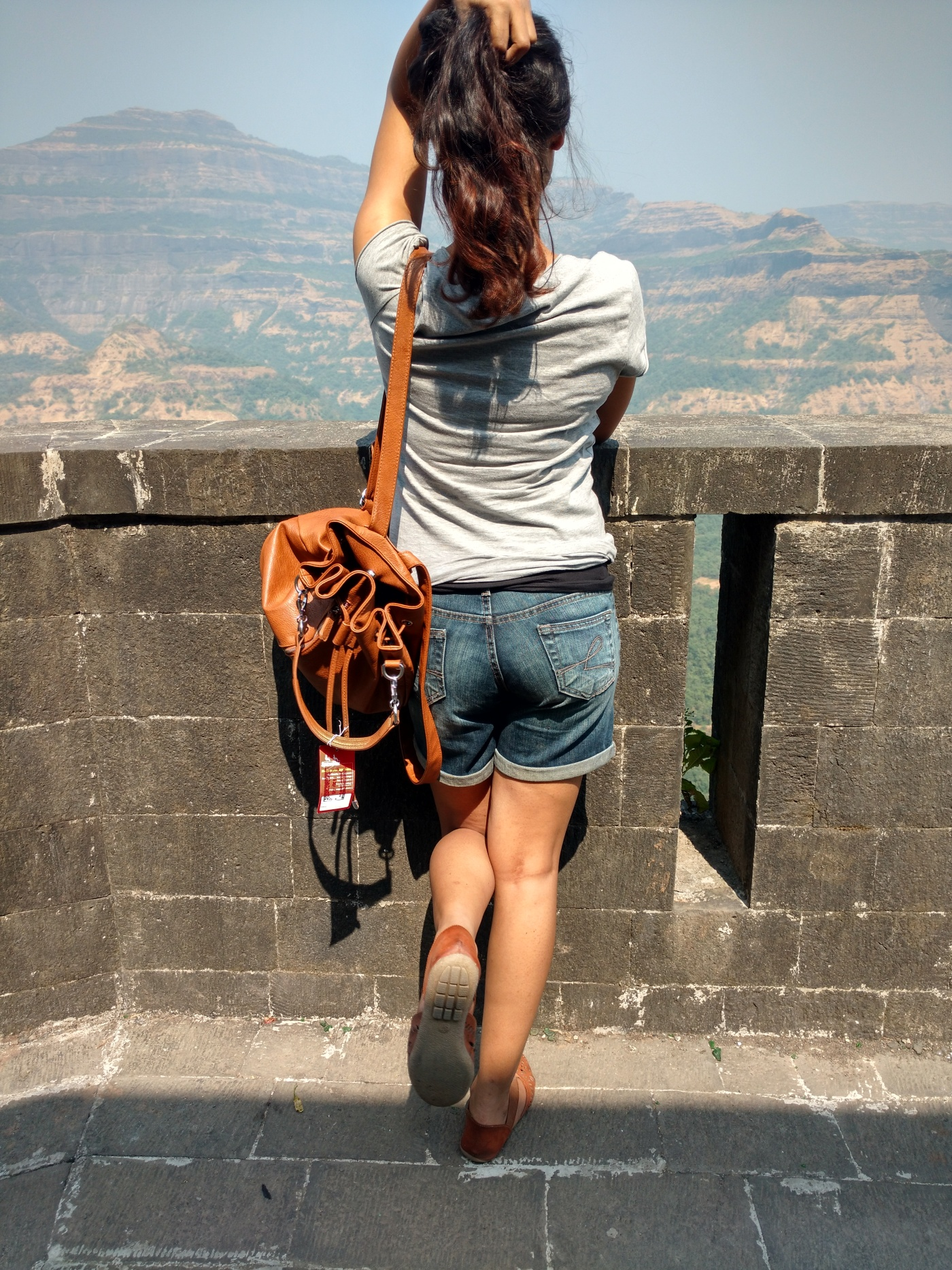 Backpacking in denim shorts and basic grey tee